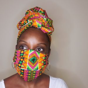 black woman in african print head wrap and mask gele